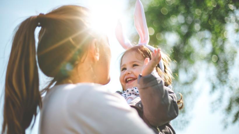 Una donna tiene in braccio una bambina con orecchie da coniglio