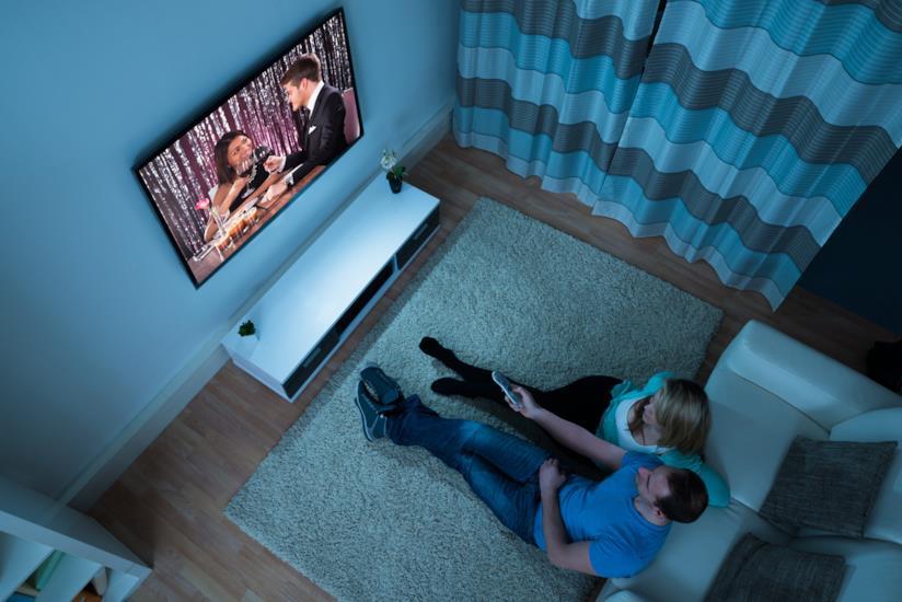 Una coppia seduta in sala guarda insieme uno show televisivo