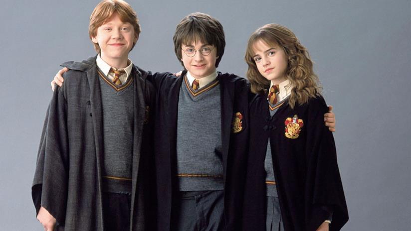 Harry Potter, Hermione Granger e Ron Wesley, vestiti da maghi, abbracciati, in posa