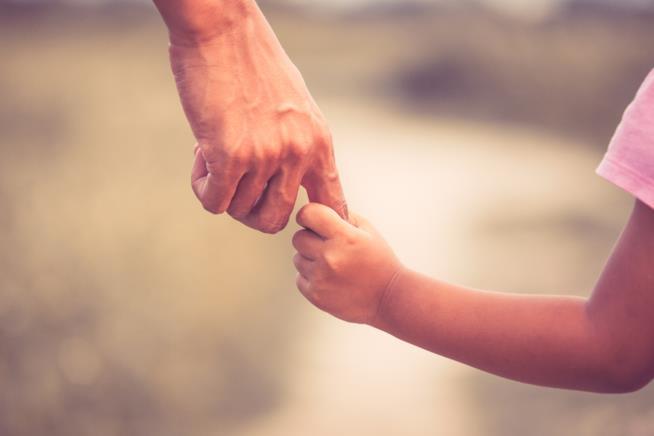 Un padre tiene per mano sua figlia
