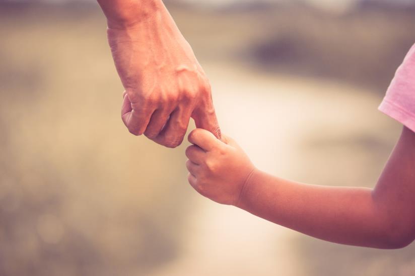 Una bambina tiene il padre per mano