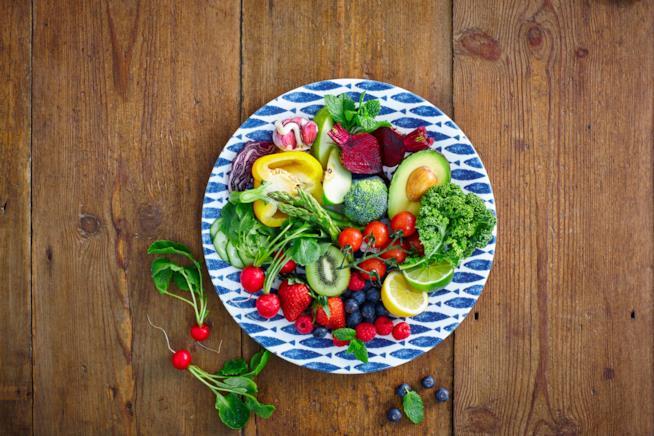 Piatto con frutta e verdura al centro di un tavolo di legno