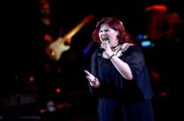 Maryam Tancredi, in piedi, vestita di nero, mentre canta al microfono