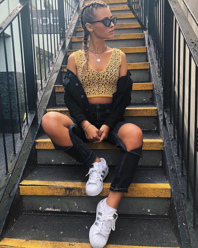 Gaia Cormio seduta sulle scale con top e jeans strappati