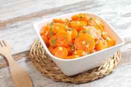 Tegame quadrato di porcellana su sottopentola di paglia intrecciato con carote, aglio e prezzemolo