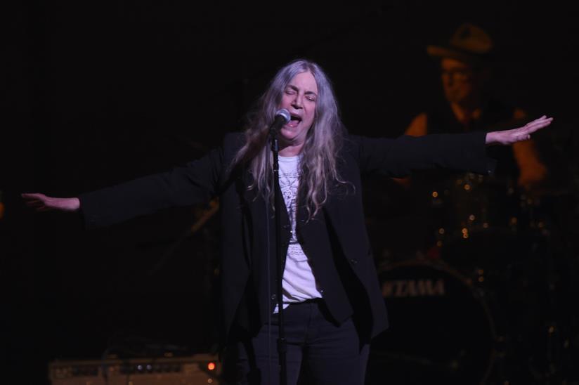 Patti Smith, in piedi, vestita di nero, canta al microfono con le braccia aperte e gli occhi chiusi