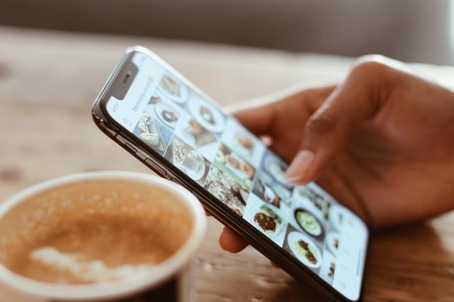 Mano di donna digita uno smartphone
