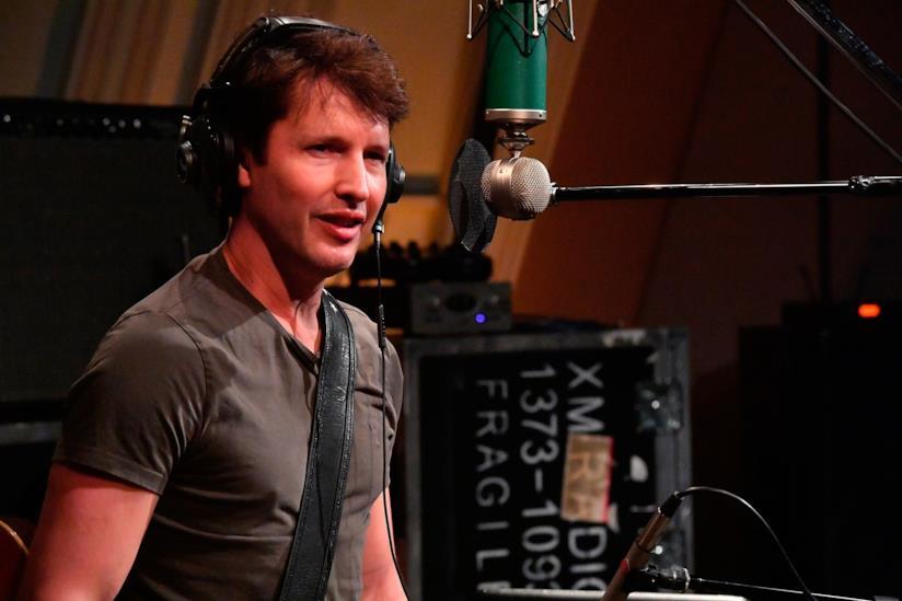 James Blunt di fronte al microfono, con una t-shirt grigia