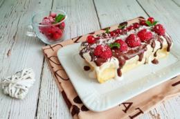Dolce bianco coperto di cioccolato e frutti rossi