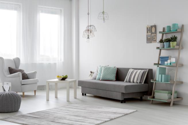 Soggiorno arredato con mobili semplici e lineari, rinnovato da accessori in colori pastello