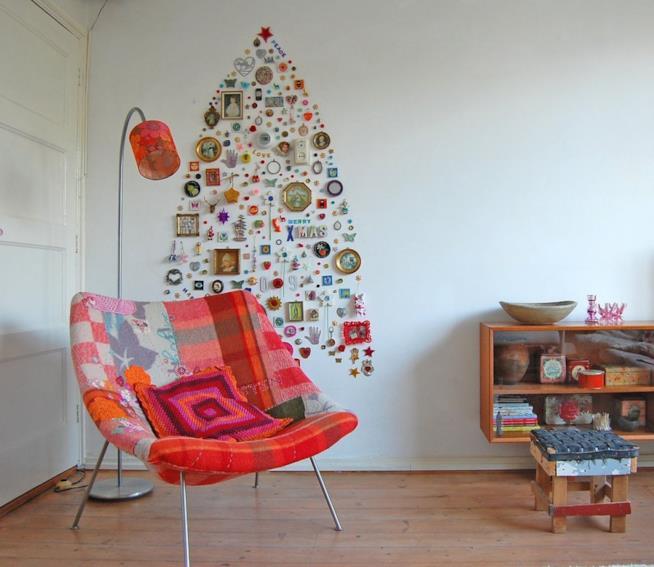 Una stanza con l'albero di Natale creato sul muro con una serie di oggetti