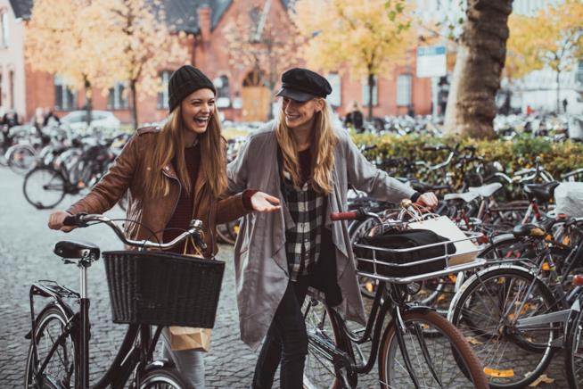 Due ragazze sorridono chiacchierando mentre passeggiano con le loro bici
