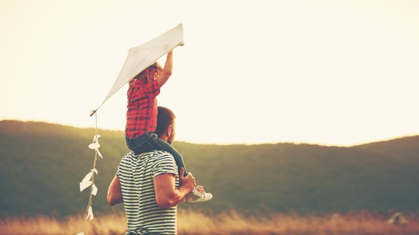 Un padre porta sulle spalle sua figlia con un aquilone