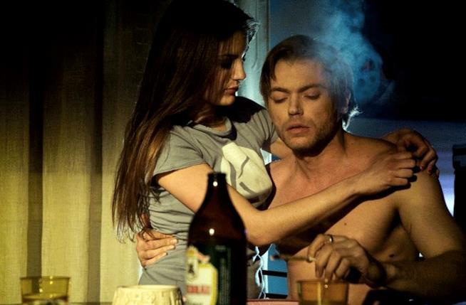 Davide Rossi a petto nudo, seduto, mentre fuma, abbracciato da Laura Gigante