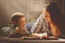 Una mamma e sua figlia mentre leggono un libro.