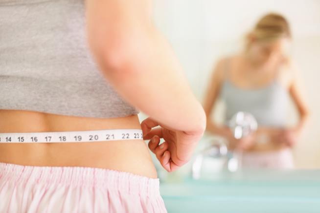 Una ragazza allo specchio si misura con il centimetro