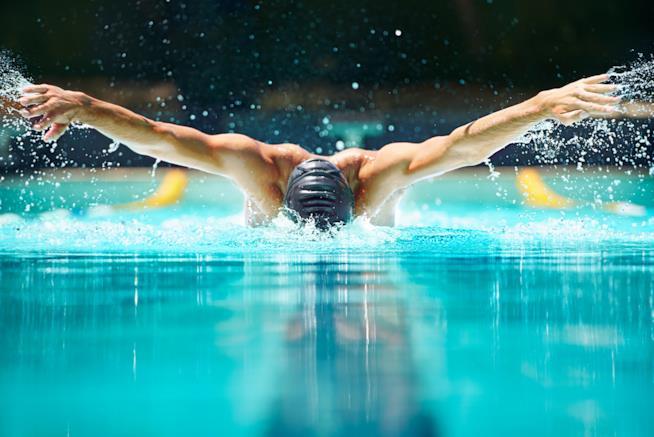 Un ragazzo avanza nuotando in piscina con lo stile farfalla