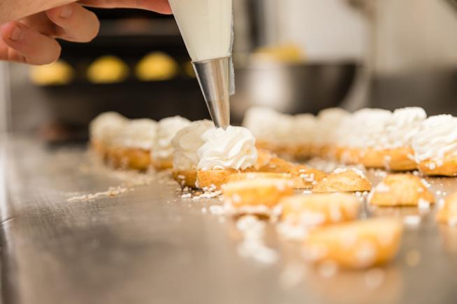Crema inserita su pasticcini con una sa