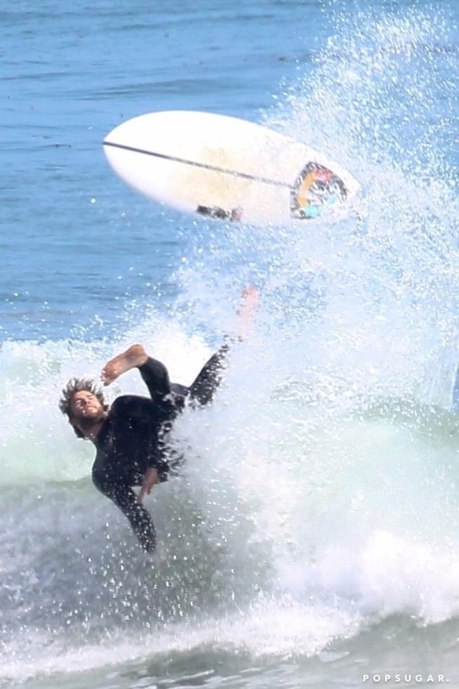 Liam Hemsworth cade durante il surf
