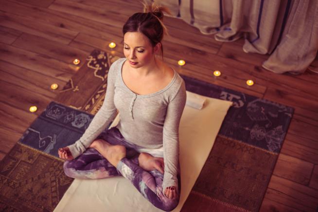Una ragazza fa meditazione seduta a terra