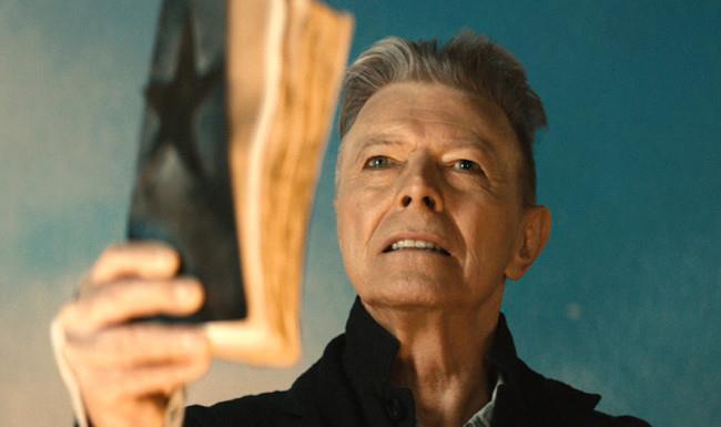 Un'immagine dal video di Blackstar di David Bowie, mentre alza il libro con la stella nera