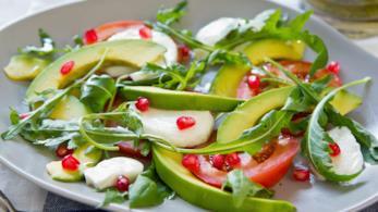 Primo piano su piatto bianco di avocado, mozzarella, rucola e melograno