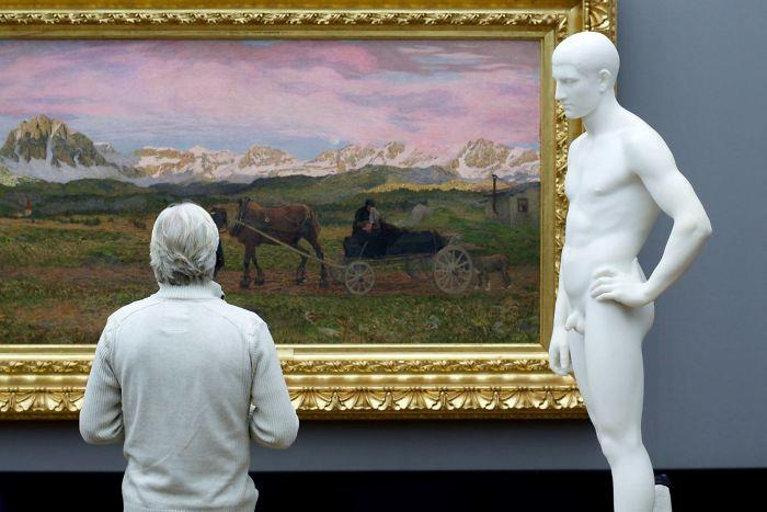 UN uomo ammira un quadro accanto ad una statua
