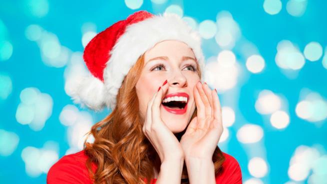 Un ragazza dai capelli rossi con indosso un cappello da Babbo Natale