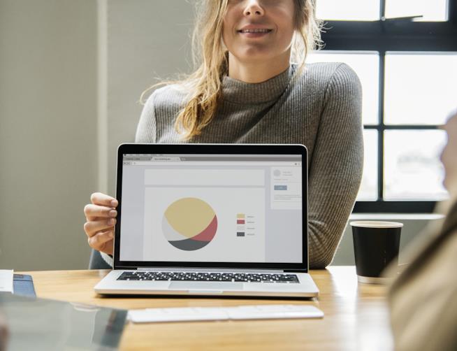 Una donna con il computer acceso davanti.