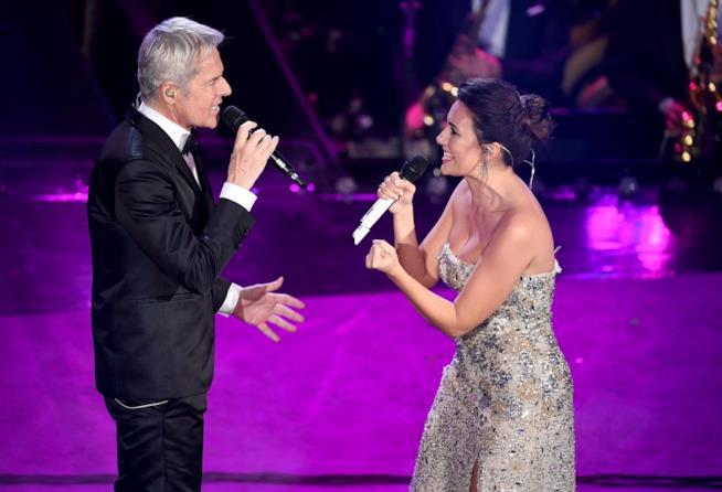 Serena Rossi e Claudio Baglioni, uno di fronte all'altro, cantano al microfono su sfondo viola