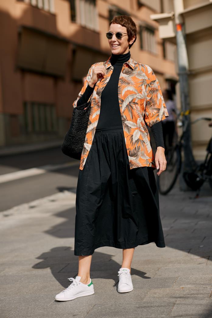 Sneakers bianche indossate con maxi dress nero
