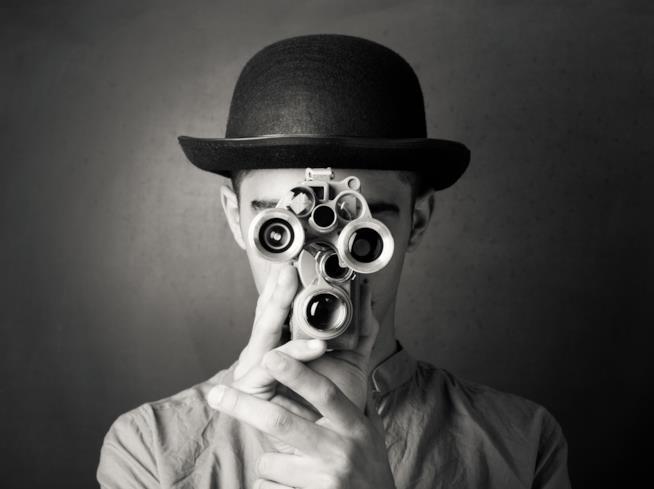 Un uomo vestito come Charlie Chaplin guarda in un caleidoscopio