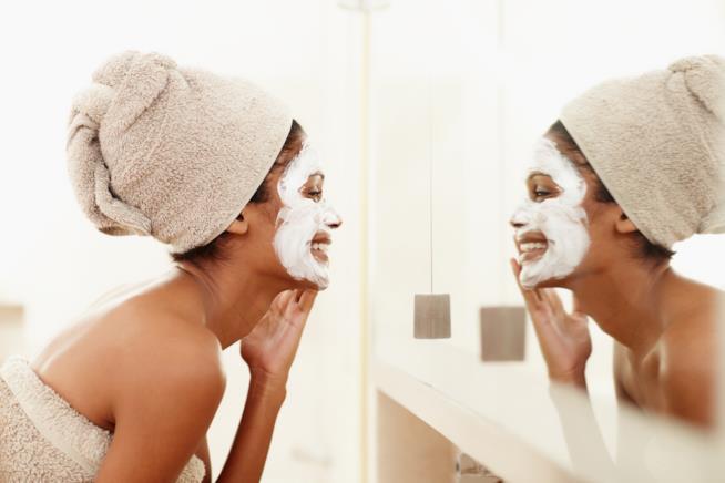 una ragazza si specchia e sorride con una maschera in viso