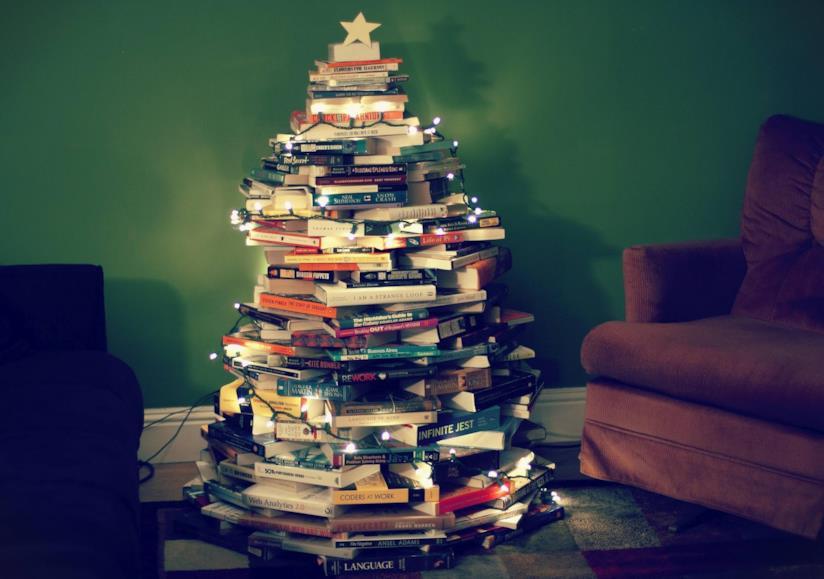 Libri disposti in modo tale da formare un albero di Natale e illuminati da luci decorative