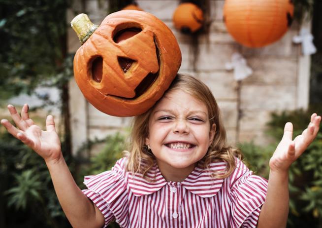 Bambina con una zucca di Halloween in testa