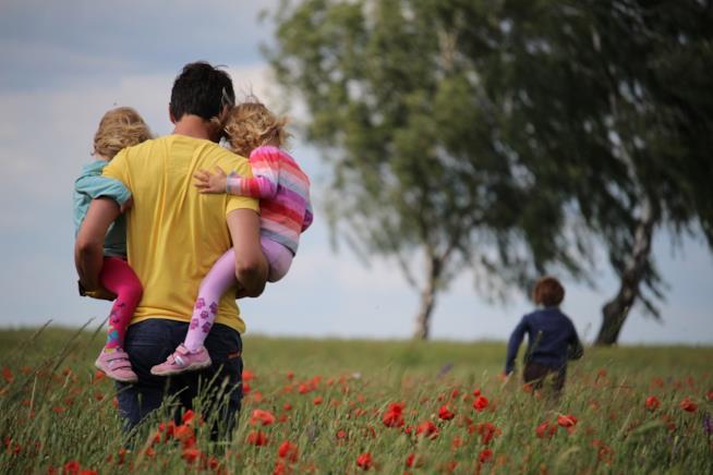 Una mamma passeggia nel verde con i figli