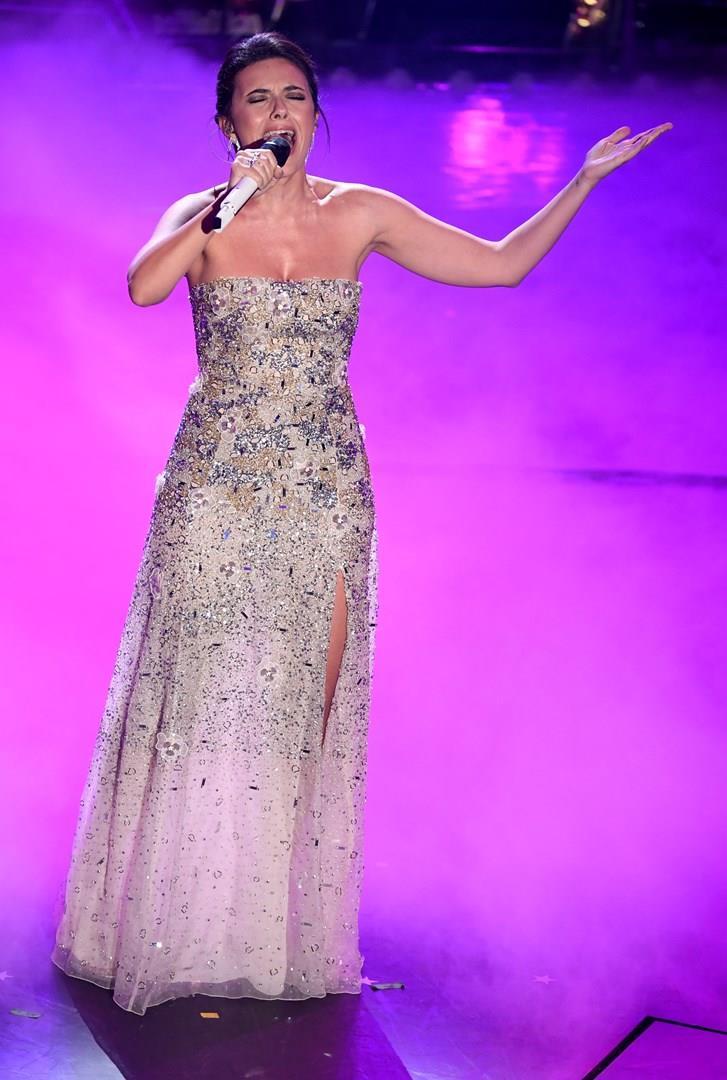 Serena Rossi, in piedi, con un lungo abito, mentre canta al microfono su sfondo viola