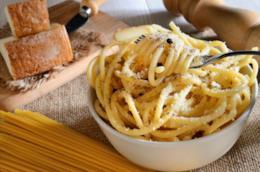 Spaghetti cacio e pepe con formaggio stagionato e macinapepe