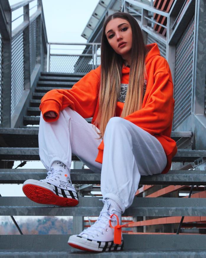 Alice Farri in outfit street bianco e arancione con converse x Off White