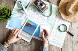 Cartina con macchina fotografica, tablet e capello