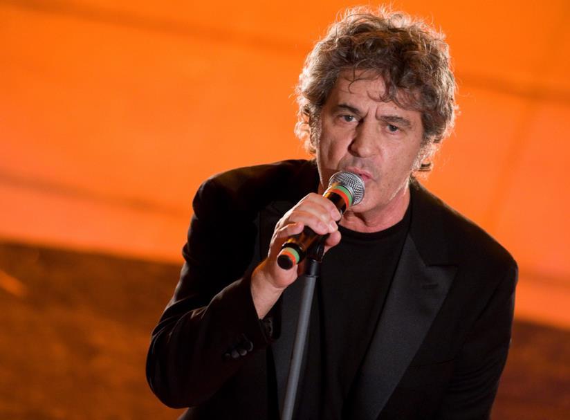 Primo piano di Fausto Leali, in nero, che canta al microfono su uno sfondo arancione