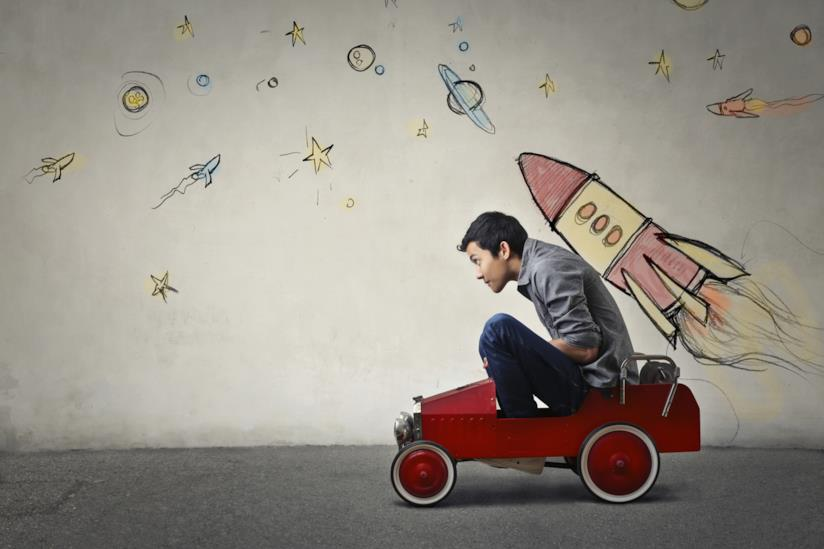 Un uomo a bordo di una macchina giocattolo con un razzo disegnato sulla schiena