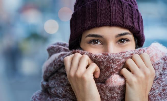 Primo piano di una ragazza con sciarpa e cappello