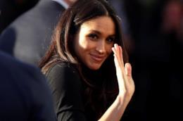 Meghan Markle mentre saluta i fotografi