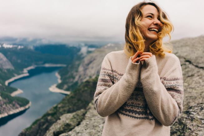 Una ragazza con un maglione sorride con, sullo sfondo, un fiordo