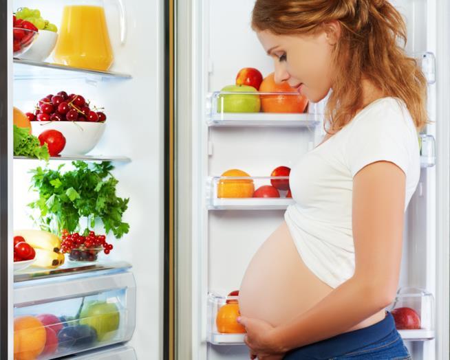 Donna incinta vicina al frigorifero