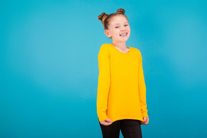 Bambina sorride di fronte alla fotocamera