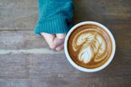 Mano di donna con una tazza di cappuccino