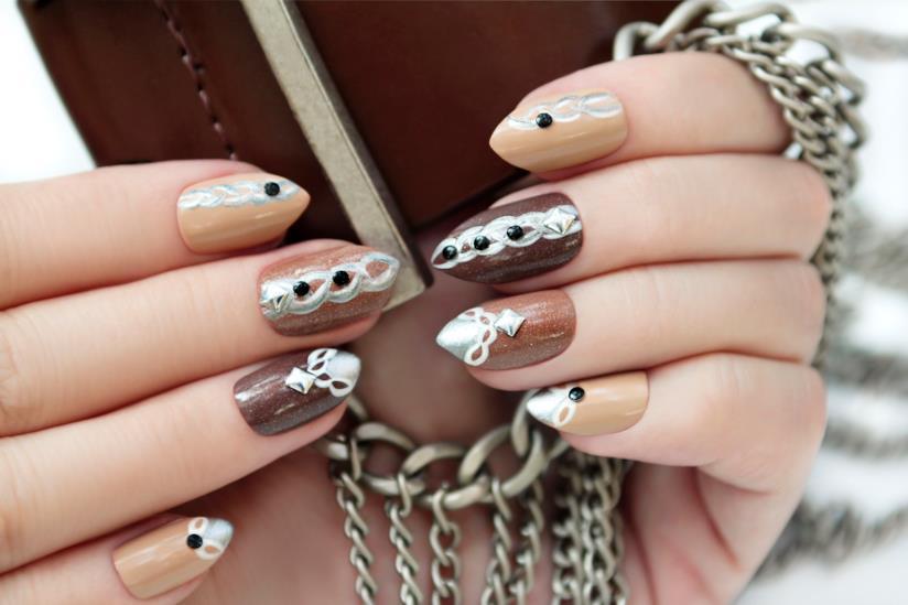 Nail art marrone con cristalli, perle e disegni