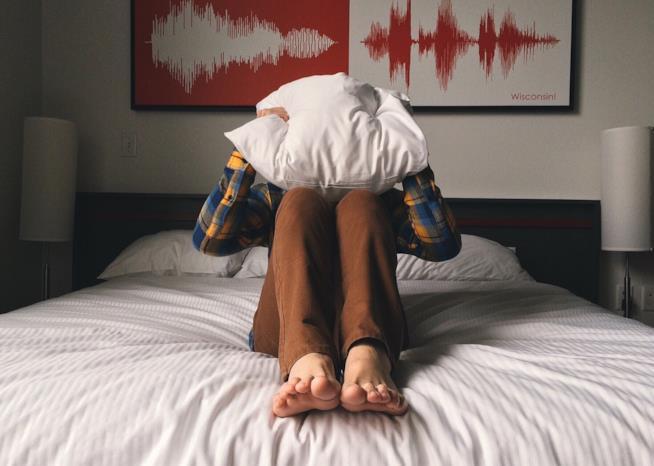 Una persona con la testa coperta dal cuscino.